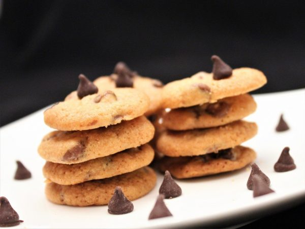 chocolate chip cookies on a plate with chocolate scattered around.