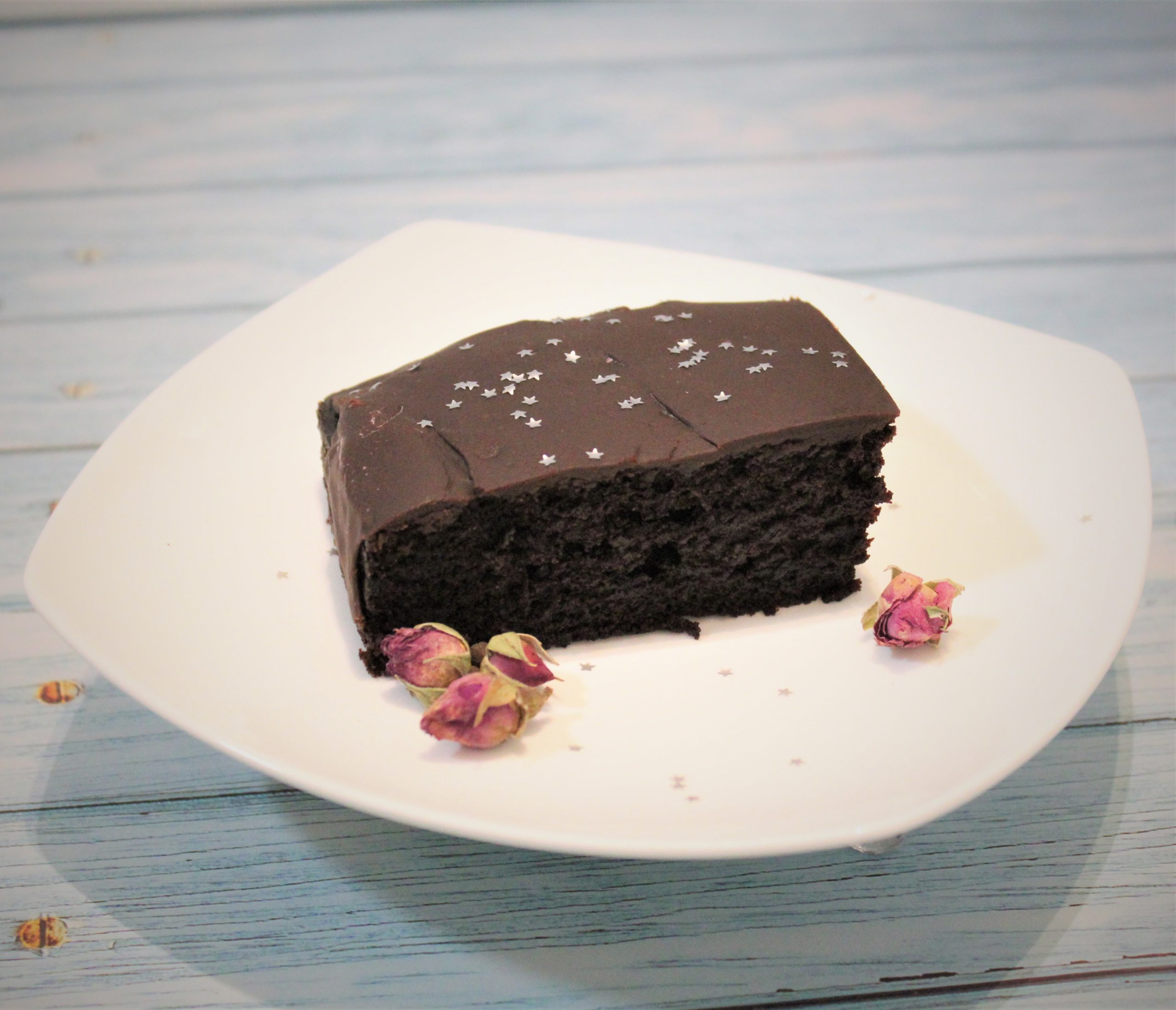 A moist chocolate cake on a plate, decorated with rose buds.