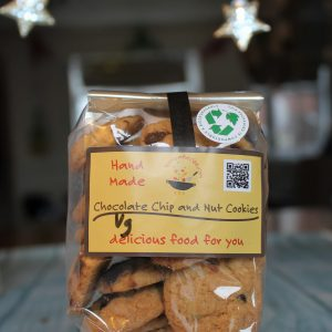 A pack of vegan chocolate and almond nut cookies. Packed in bio-degradable packaging.