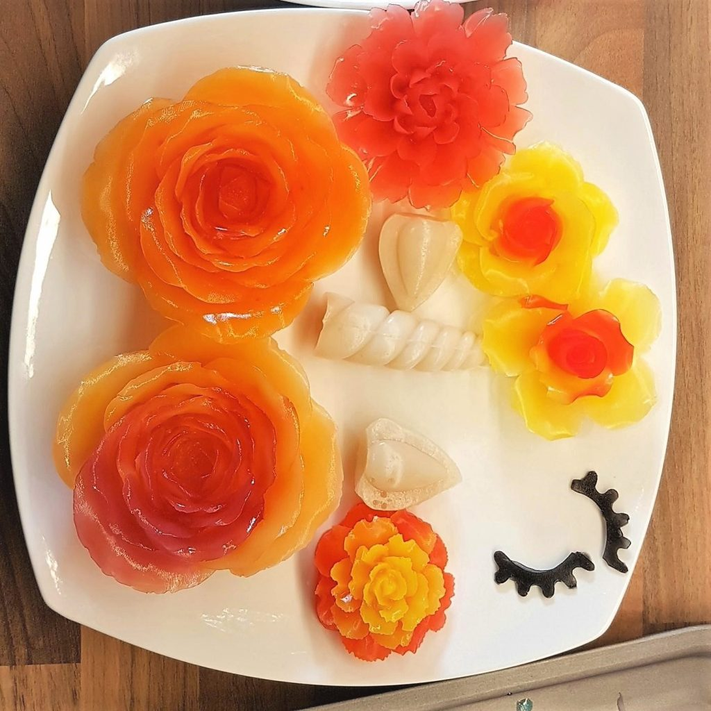Flowers in various orange hue and unicorn horn, ears and eyes.