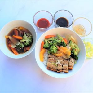 Roast pork dinner with vegetable stir-fry and dips.